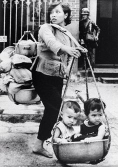 A Vietnamese woman carries her children and possessions on bamboo pole as she tries to escape fierce fighting in the Cholon suburb of Saigon during the Viet Cong Mini Tet offensive of the Vietnam War in May 1968 --- Image by © Nik Wheeler/Corbis