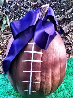Tailgate centerpiece: Football pumpkin with a purple ribbon.