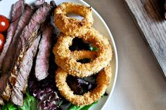 Healthy, crunchy Onion Rings (& A Grilled Steak) |  Last week Ina made Jeffery some fried onion rings and juicy filet with creamy blue cheese sauce so rich that it could instantly induce a heart attack. I figured I could bake the onion rings and make them super crispy and crunchy. They don't get soggy like deep fried onion rings do.  They stay super crunchy and sweet. | From: howsweeteats.com
