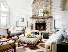 Log cabin living space with stone fireplace and painted white wood walls