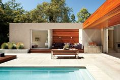 Great, versatile outdoor space with dining, lounge, kitchen, and pool. Love the open flow between indoors and outdoors, and the unexpected purple accents, too. Designed by Matthew Mosey.