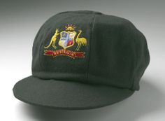 A colour photograph of a baggy green cricket cap. The cap has a large peak and the Australian Coat of Arms stitched onto the front panel. There is what appears to be a button on the crown of the cap. The cap has been photographed against a white background. It casts a soft shadow on the background.