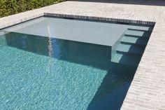 Minimalistisch betonnen skimmer zwembad met ruime plage en ingebouwde hoektrap ‹ De Mooiste Zwembaden