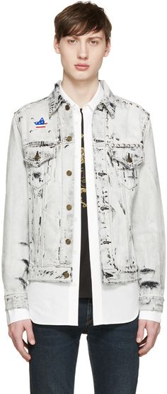 Long sleeve denim jacket in pale grey. Bleached wash. Distressing throughout. Spread collar. Button closure at front. Flap and welt pockets at body. Embroidered star appliqué at front yoke in white, blue, red, and silver-tone. Hemisphere studs in silver-tone at front and back yokes. Single-button barrel cuffs. Buttoned cinch-straps at hem. Patch pockets at interior. Unlined. Contrast stitching in black.