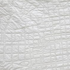 City quilts: beautiful and subtle street maps hand-stitched onto white quilts.