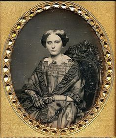 """Auction Catalogue from Be-Hold:  Be-hold photographs: """"Collector's Joy."""" FASHIONABLE WOMAN, 1/6 PLATE DAGUERREOTYPE. . No maker is named, but the woman is seated on a fancy posing chair, indicating a prosperous studio."""