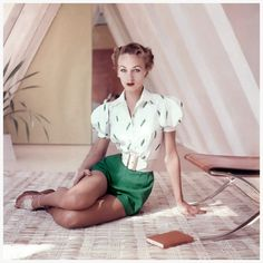 """Model, about to read book, wearing green shorts, white cotton shirt embroidered with pea pods and a wide, cinched belt, 1952. Condè Nast Archive. Photo Frances McLaughlin-Gill. Frances McLaughlin (the hyphenated """"Gill"""" was added after her husband died) characterised her photographs as occupying a """"narrow fringe"""" between """"the sharp, sharp details of the long-exposed image"""" and the """"blurred fantasy of the out-of-focus picture."""""""
