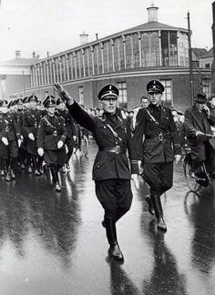 Tweede Wereldoorlog, Nederlandse SS-ers, manifestaties. Een mars van de Nederlandse SS, op de pet geen doodskop maar een wolfsangel van de NSB, door de stad Groningen onder leiding van Onderstormleider J.P. Wolffram. Nederland, Groningen, 8 april 1941.