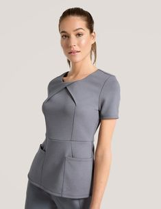 The Envelope Pleat Top in Graphite is a contemporary addition to women's medical scrub outfits. Shop Jaanuu for scrubs, lab coats and other medical apparel. Dental Uniforms, Healthcare Uniforms, Spa Uniform, Scrubs Uniform, Dental Scrubs, Medical Scrubs, Stylish Scrubs, Scrubs Outfit, Cute Skirt Outfits