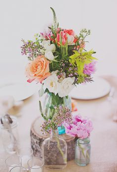 Brides: Colorful Mason Jar Centerpieces. Mismatched mason jars filled with colorful flowers are placed upon wooden rounds and burlap runners to create a charming tablescape.