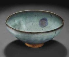 A PURPLE-SPLASHED JUNYAO BOWL YUAN DYNASTY (1279-1368) The bowl is covered inside and out with a thick, crackled blue glaze with faint purple-toned streaking. A purple splash accentuates the interior. 7¼ in. (18.4 cm.)