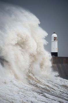 Waves crash against the harbour wall in Porthcawl, South Wales