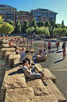 Jamison Square in Portland, OR, by PWP Landscape Architects - photo from Behance; Jamison Square is a one-acre park featuring a complex stepped stone wall. The park design includes three main elements: a fountain, a boardwalk, and an outdoor gallery. When the fountain is turned off, the space functions as a shady plaza for special events. The stepped stone walls can be used as bleacher seating for small or large crowds.