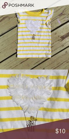 Striped Love Parachute Flutter Sleeve Shirt Yellow and white shirt with flutter sleeves. It's adorned with a sparkly print of a girl and her dog in a hot air balloon. The balloon itself is an adorable white heart appliqué. 100% cotton Carter's Shirts & Tops