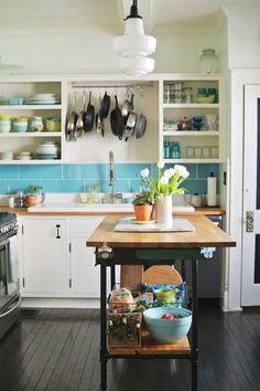 Fabulous kitchen set-up. I love the open cabinet shelving and the large island. And the turquoise subway tile is to die for!