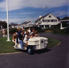President Kennedy gives younger Kennedys a ride on a golf cart.