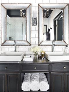 Chosen for its antiqued black finish, this entry console was retrofitted as a custom vanity, which contrasts sharply against the white, subway tile-covered walls. To blend different finishes against the all-black-and-white palette, antique brass knobs were installed along the vanity's drawers and door fronts; polished chrome farmhouse faucets were used to accompany the white porcelain vessel sinks; and zinc-framed mirrors were installed on the wall to help pull together the silver and brown ...
