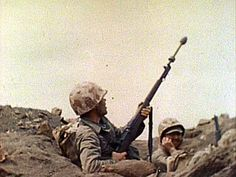 A rifle grenadier engages a target on Iwo Jima. Attached to the M1 rifle, the grenade launcher was a useful weapon for high angle fire. Still image from USMC combat camera film