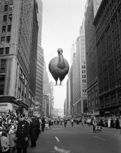 1957: A giant floating turkey balloon squeezes between buildings as the 31st annual Macy's Thanksgiving Day Parade moves down Broadway near ...