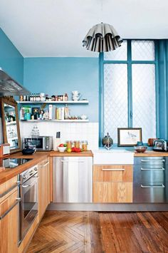 Bright blue kitchen with wooden cabinets and flooring, white shelving and backsplash tile, and a silver pendant light fixture.