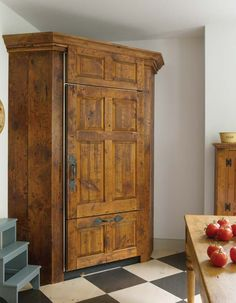 The Sub-Zero refrigerator/freezer hides in a corner cabinet built from antique lumber with an unpainted tung oil finish.