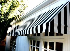 black and white striped awnings on a white house.  dark grey door?