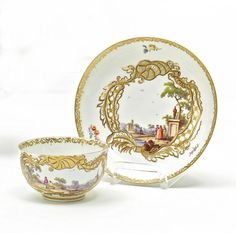 Cup and Saucer with Landscape Scenes.   Meissen. Circa 1740-45.     Porcelain, enriched in colours and in gilt. Narrow, gold lace border and scattered flowers along the inner edges. Each piece decorated by a large cartouche with dark contours, framing a finely wrought landscape with figural staffage. Height 5cm/ + 13,5cm.  Crossed swords mark, the number 69 in purple (presumably added later). Saucer with the press number 63 and the collector's label 'Porzellan Sammlung Rudolf Weigang'.