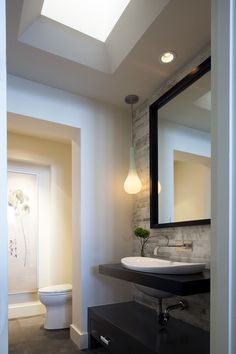 Contemporary Powder Room with Powder room, Wall faucet, Drop-in sink, Flat panel cabinets, Inset cabinets, Stone tile wall