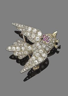 A ruby and diamond bird brooch, circa 1900  Set throughout with rose, old brilliant-cut and cushion-shaped diamonds, the head decorated with oval-cut rubies, to engraved detailing on the wings, mounted in silver and gold, diamonds approx. 0.65ct total, detachable brooch fitting, length 3.3cm