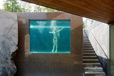 9 – Au milieu des rochers, l'eau A la façon d'une fenêtre, la vitre donne à voir l'eau et les baigneurs au milieu d'une paroi très minérale, faite de béton et de rochers.
