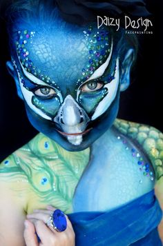 The only way you know it's not a real peacock is because of the ring. | The Most Elaborate Face Painting In TheWorld