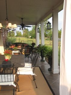 """Patio divided into a living room and dining room. Note chandelier over the dining area, & ceiling fan above the """"living room."""" I also like how the rug further defines the dining space."""