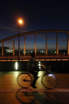 犀川、御影大橋はここ数十年の間に金沢旧市街に架かった橋の中でひときわ美しくまた独創的だと思う。  石川県初の単弦ローゼ橋という一本のアーチで支える構造は上流側の景観を遮る構造を無くすために採用され、 またその景観を楽しめる歩道は上流方向に向かって中央部分が緩やかに曲線を描く凝った構造になっている(上流の犀川大橋、上菊橋と同様「景色を眺めるため」のベンチも設置されているの金沢らしい配慮)   'いもり堀脇'などと同様に歩道路面だけを照らす様にデザインされたシンプルでモダンな照明、アーチを印象的に浮かび上がらせるナトリウム灯照明、夏の色濃い夕暮れが見事に調和して出現した'日常'の中の一コマ。 2018年07月26日 19時56分 Kanazawa, Scenery, Night, Landscape, Paisajes, Nature