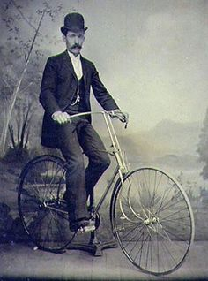 A vintage portrait of a hirsute gentleman with a remarkable moustache and a bicycle.