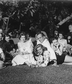 Vivien Leigh with her daughter Suzanne seated behind Joan Bennett, Lauren Bacall, Humphrey Bogart, Nadia Gardiner, and various others gathered on the lawn of the Clifton Webbs' photographed by Jean Howard
