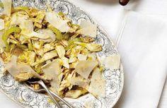 L'insalata di carciofi crudi si prepara eliminando le foglie esterne più dure dei carciofi, e poi affettandoli e disponendoli sulle fettine di parmig...