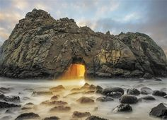 Light emanates from a natural arch in a rock off Pfeiffer Beach in Big Sur, Calif. The amazing glow can be seen only a few weeks of the year, when the sun sets directly behind the arch. For the yellow rays to shine through the Keyhole Arch, the tide must be high enough to reflect the sun's light perfectly. The phenomenon lasts only about five minutes before the sun sets.