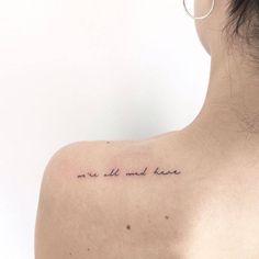 """Tatuaje que dice """"We're all mad here"""" (""""Todos estamos locos aquí"""") de Alicia en el País de las Maravillas, situado en el omoplato izquierdo."""