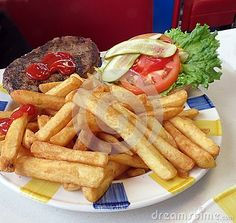 A hamburger with the works, along with a side order of French fries at the diner.