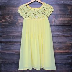 Gorgeous flowy yellow dress that features a pleated front, cap sleeves, and a sheer yoke upper. - imported - 100% polyester - fully lined body - relaxed fit