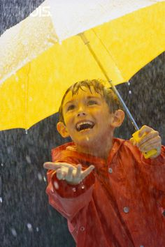 Boy with umbrella reaching one hand out to touch the rain