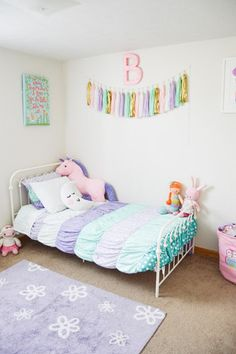 Use pastel colors to create a fun and whimsical vibe like this room. The unicorn and moon stuffed animals complete the room.