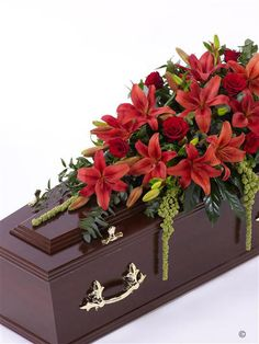 Lily and Rose Casket Spray - Red 4ft. This striking casket display features a selection of fresh Asiatic Lily and large-headed Rose in shades of rich red. The flowers are carefully arranged with amaranthus, ruscus, eucalyptus and aralia leaves. Approximate height 122cm (4ft)