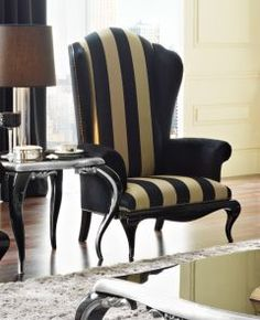 Add the Luxury designer wing chair shown here in our satin black and gold stripe and black velvet fabric and create a luxurious atmosphere. Upholstered on to a black lacquered gloss frame with stud detail. Fabulous in any setting!