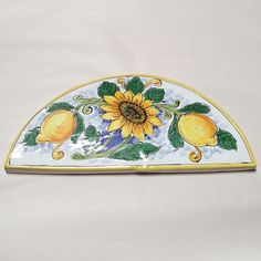 Wide Arch-Shaped Tile - Sunflower & Lemons - handmade, hand painted Italian First Stone tiles. These tiles were inspired by a 16th century Italian tradition of placing stones on walls of new homes and gardens to assure blessings and prosperity. A perfect housewarming gift. Found at the Italian Pottery Outlet in Santa Barbara CA