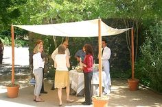 good idea using the potted plants for the base of a DIY awning