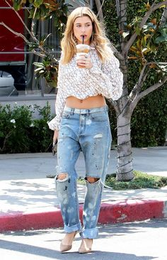 Hailey Baldwin keeps it California casual in a pair of distressed denim with a cropped shirt and heels