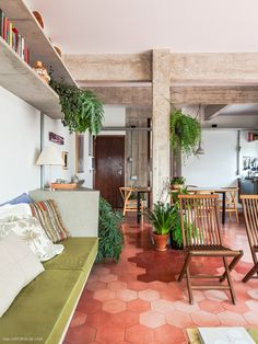 Sofá com estrutura de concreto ganhou assento na cor verde e muitas almofadas. Destaque especial para o piso hexagonal em tons de terra.