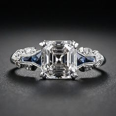 A glorious and glistening classic square emerald-cut - aka Asscher-cut - diamond is the star attraction of this showstopping engagement ring, crafted in platinum and accented with calibre-cut faceted sapphires - circa 1930s
