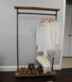 This garment rack is built for narrower spaces from iron piping and mildly distressed wood, yet has double the storage space with a top and bottom shelf. It will add a touch of class to a loft, office, rustic style home decor, and an industrial space. Base depth = 11 1/4 Base Width = 36 Height = approximately 57. The hanging space is approximately 49 high. We provide two rotating casters on one end at no additional charge, with two fixed castors on the other end. The casters are upgraded…